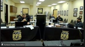 Screenshot from PPA contract negotions Zoom call. PPA officials sit at tables at computers, the front two tables are draped with a black tablecloth, with the PPA logo. The wall has a framed thin blue line flag, and the six people in the room all look like the same middle-aged white guy. The man at the front table is not wearing his mask properly, leaving his nose exposed.