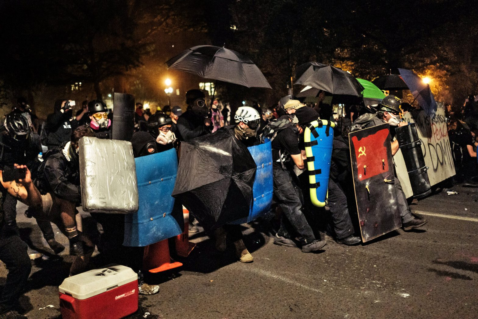 Wall of shields and umbrellas at a black bloc action in Portland