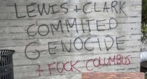 Graffiti on a wall that reads: Lewis + Clark commited genocide + fuck Columbus